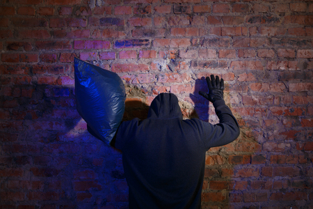 law breaking: Bandit with bag stands with arms raised in brick wall at night