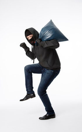 Thief in mask with blue bag slinking on pure white background