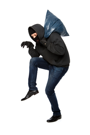 Robber in black mask sneaks with blue bag on his shoulder on blank white background Stock Photo