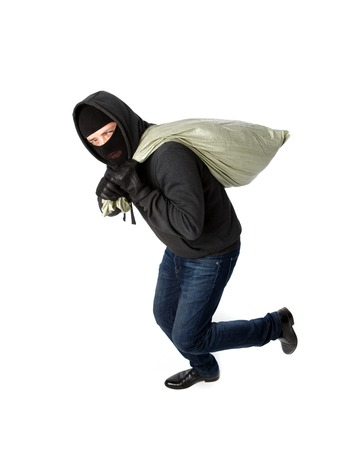 Thief running with heavy black bag on shoulder on pure white background Stock Photo