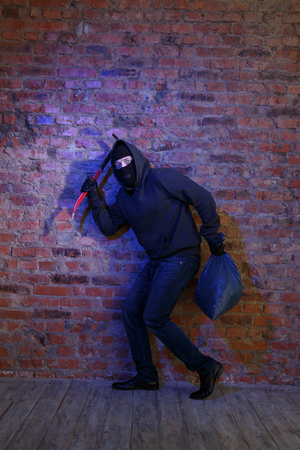 rogue: Rogue near brick wall with sack and pickaxe in hands