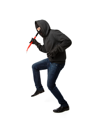 Burglar sneaks in black mask with master key on pure white background Stock Photo