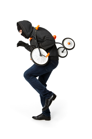 Burglar in black mask stealing childrens bicycle on pure white background