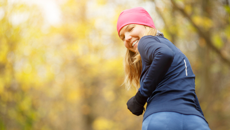 Smiling girl in pink hat on morning jog in forest