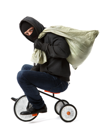Thief with bag on childrens bicycle on pure white background Stock Photo