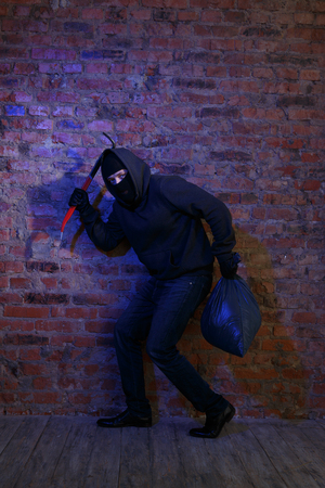 pickaxe: Crook near brick wall with bag and pickaxe in hands