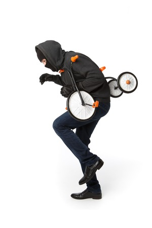 Robber in black mask steal childrens bicycle on pure white background