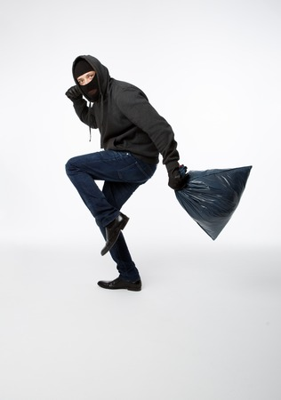 Thief slinking in black mask with heavy bag on pure white background