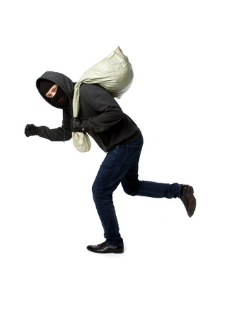 Thief escapes with full bag on empty black background Stock Photo