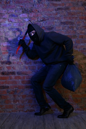 pickaxe: Thief near brick wall with bag and pickaxe in hands Stock Photo