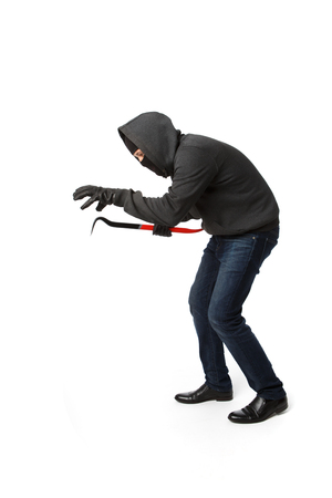 Crouching burglar with master key in his hand isolated on blank background