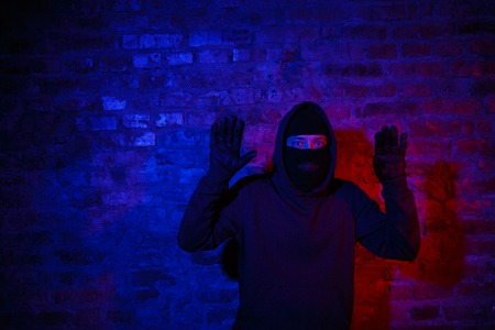 trapped: Trapped burglar standing at night near brick wall