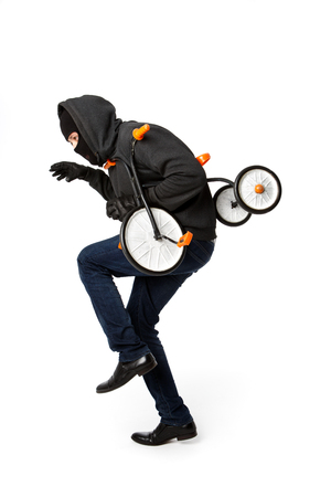 Robber sneaks with child bicycle in hands on white background
