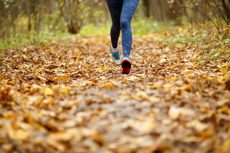 Woman in sneakers running through woods in autumn Stock Photo