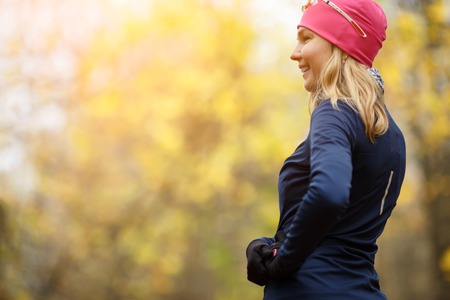 athletic girl standing back in autumn forest morning Stock Photo