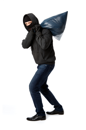 Thief carries heavy big bag on his shoulder on pure white background Stock Photo
