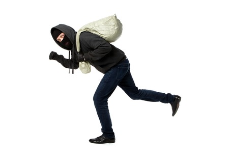 Thief in jacket with hood escapes with bag of loot in empty white background Stock Photo
