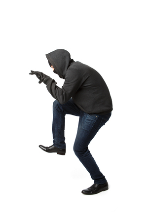 Crouching thief with master key in his hand isolated on blank background