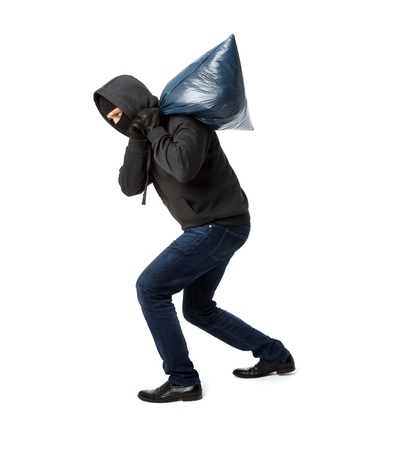 Thief in black gloves carries heavy bag on his shoulder on a blank white background