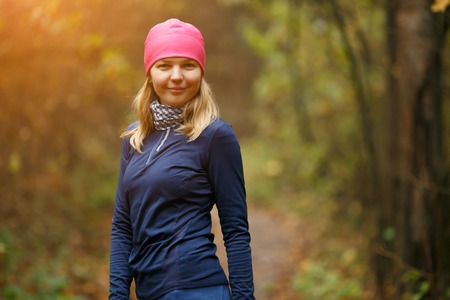 Smiling girl in sport wear in autumn forest