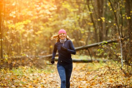 Blonde woman running in morning in autumn forest
