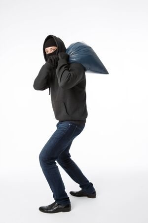 Thief in mask with bag on his shoulder on pure white background