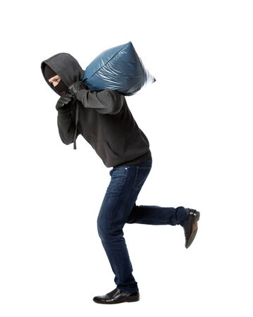 Thief in black gloves escapes with heavy bag on his shoulder on blank white background