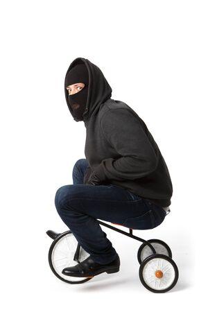 Burglar in black mask on childrens bicycle on white blank background