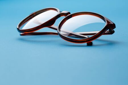 rimmed: Folded brown spectacles close up on blue background empty