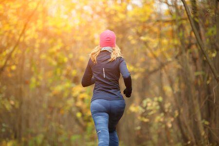 Slender female running in park in autumn Stock Photo