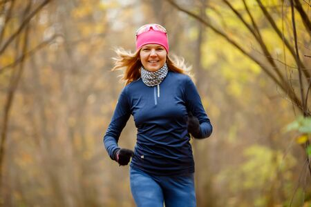 Young woman jogging in morning in autumn park