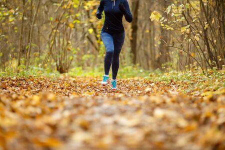 Girl in sportswear running in park in autumn