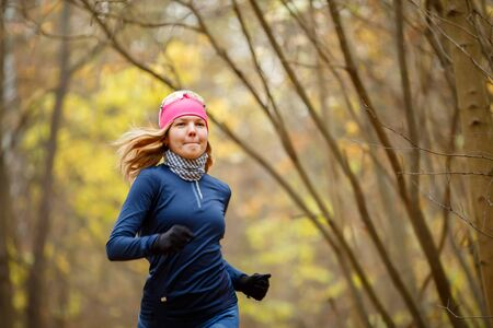 Young female running in morning in autumn forest