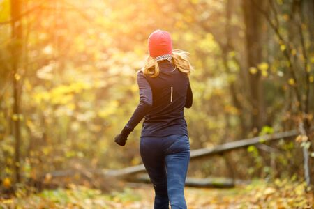 Pretty girl running in morning in autumn forest