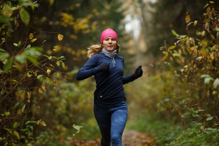 Blonde woman running in morning in autumn park Stock Photo