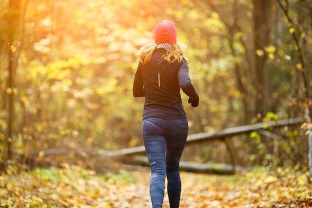Beautiful sportswoman running in morning in autumn forest