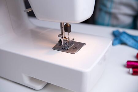 Sewing machine on table with coils of red thread and measuring tape