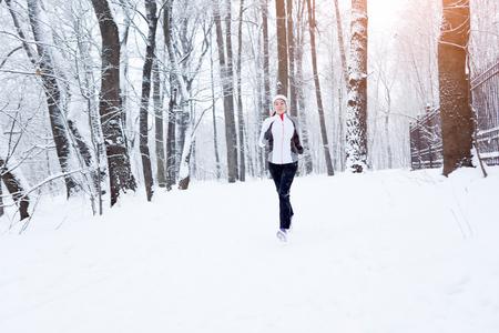 hacer footing: Hermosa morena en correr por la mañana en el parque de invierno Foto de archivo