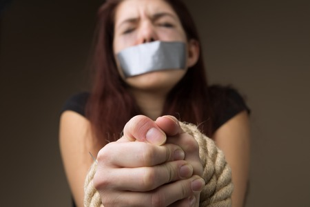 Brunette gagged and tied hands Stock Photo