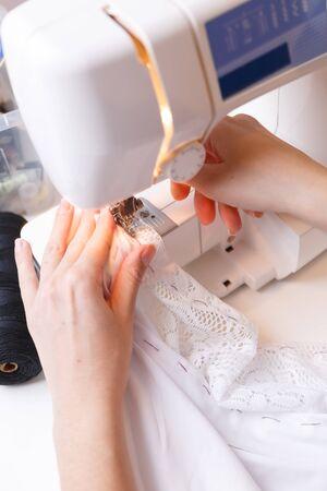 Couturière griffonne tissu sur la machine à coudre Banque d'images