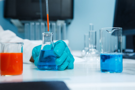 Laboratorian with flask on table Stock Photo