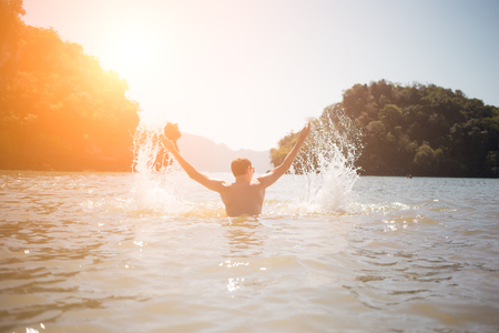 Man arms raised in sea Stock Photo