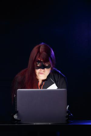 Portrait of burglar with computer