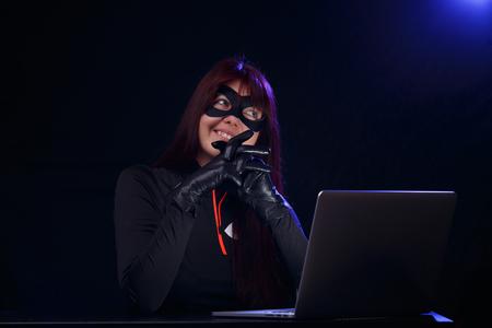 Night hacker in black mask