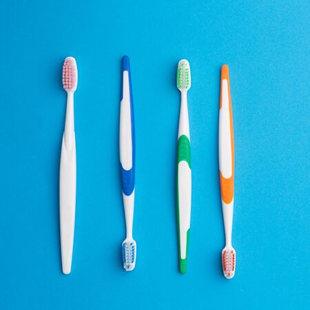 four objects: Multicolored toothbrushes on blue background