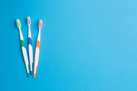 Three multi-colored toothbrushes on left at empty blue background, place for inscription
