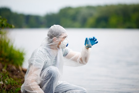 Biologist with test-tube near river