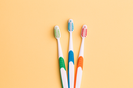 fluoride: Toothbrushes on empty orange background Stock Photo