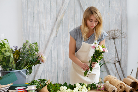 clothing store: Young blond florist makes bouquet
