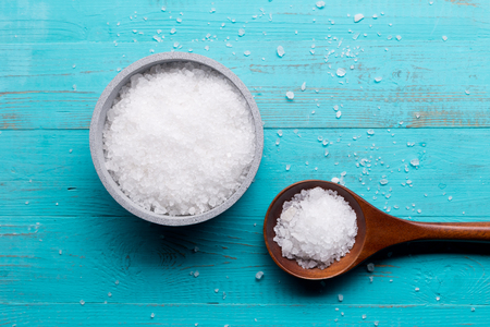 sea salt in bowl and in spoon on wooden background Zdjęcie Seryjne - 82934532